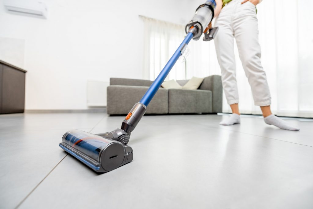 Woman cleaning floor with cordless vacuum cleaner
